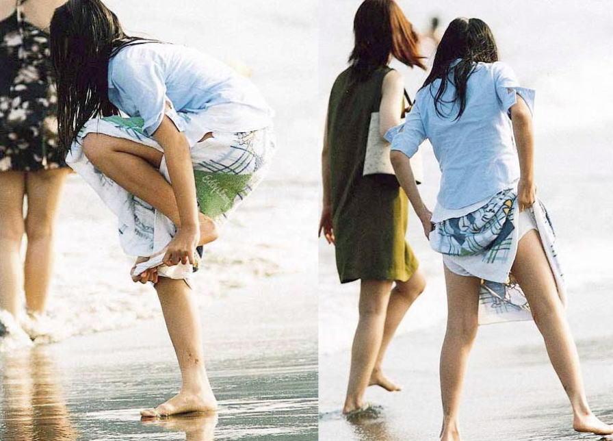 ビーチの隅で水着に着替えている女の子 (6)